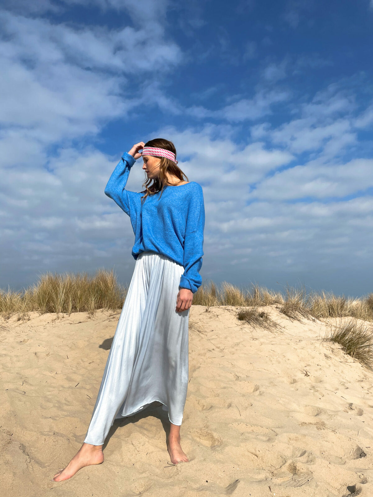 woman wearing a blue knitted top and a blue long skirt