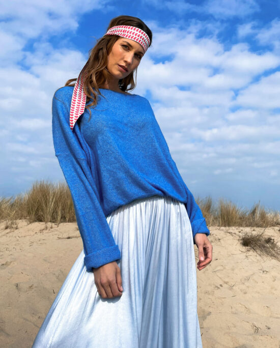 woman with a blue knitted sweater and a blue satin skirt