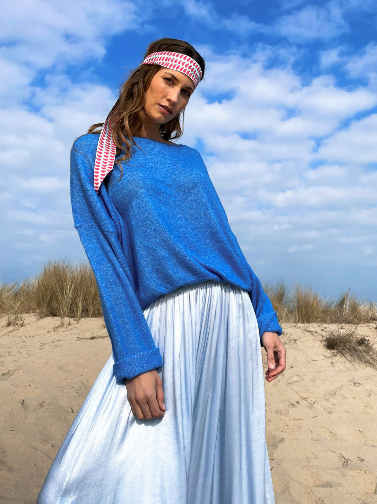 woman with a blue sweater and a blue long skirt on the beach