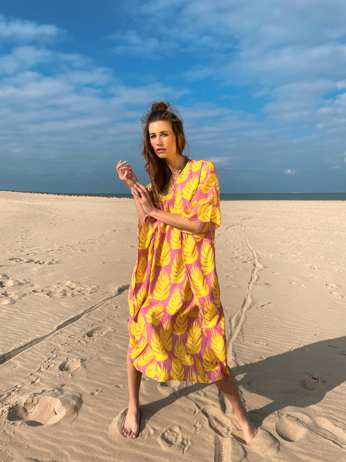 woman on the beach wearing a yellow and pink kaftandress