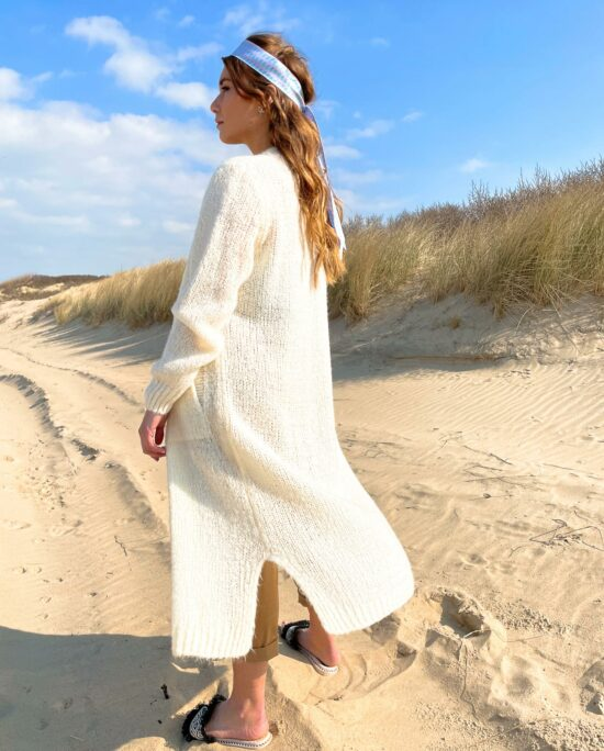 woman on the beach wearing a white long cardiga,