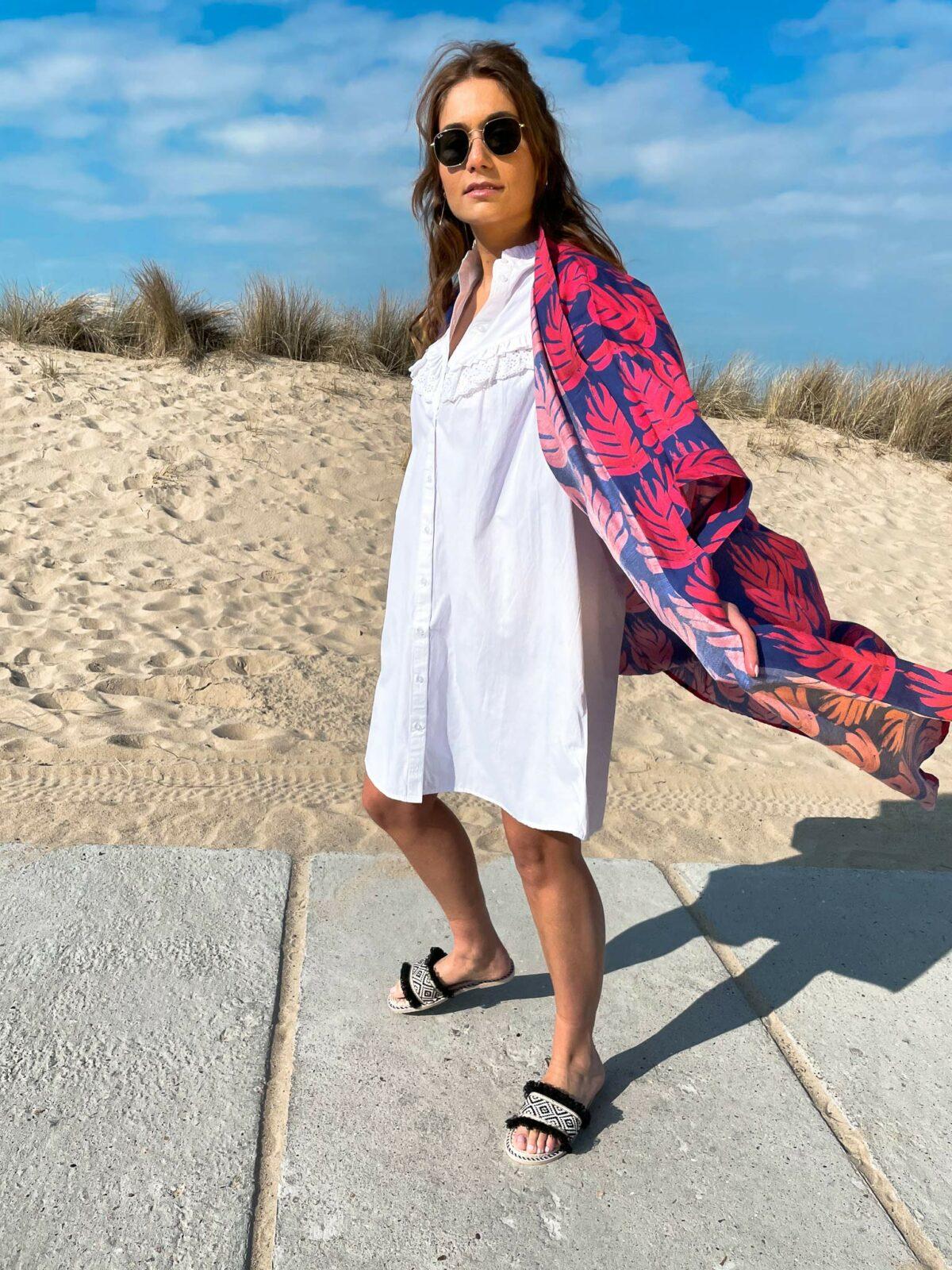 woman on the beach wearing a white dress and a fuchsia pareo