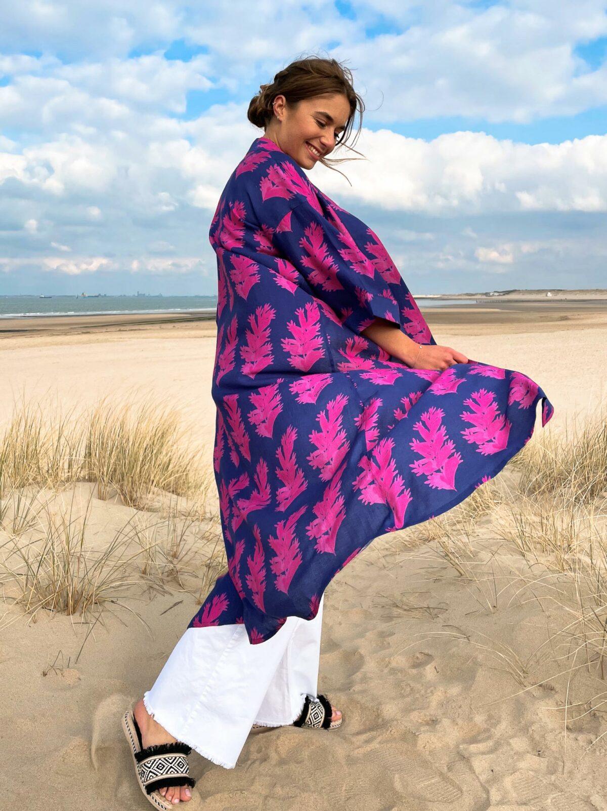 woman on the beach wearing a blue and fuchsia kimono