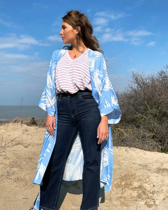 woman on the beach wearing a blue and whitekimono and denim pants