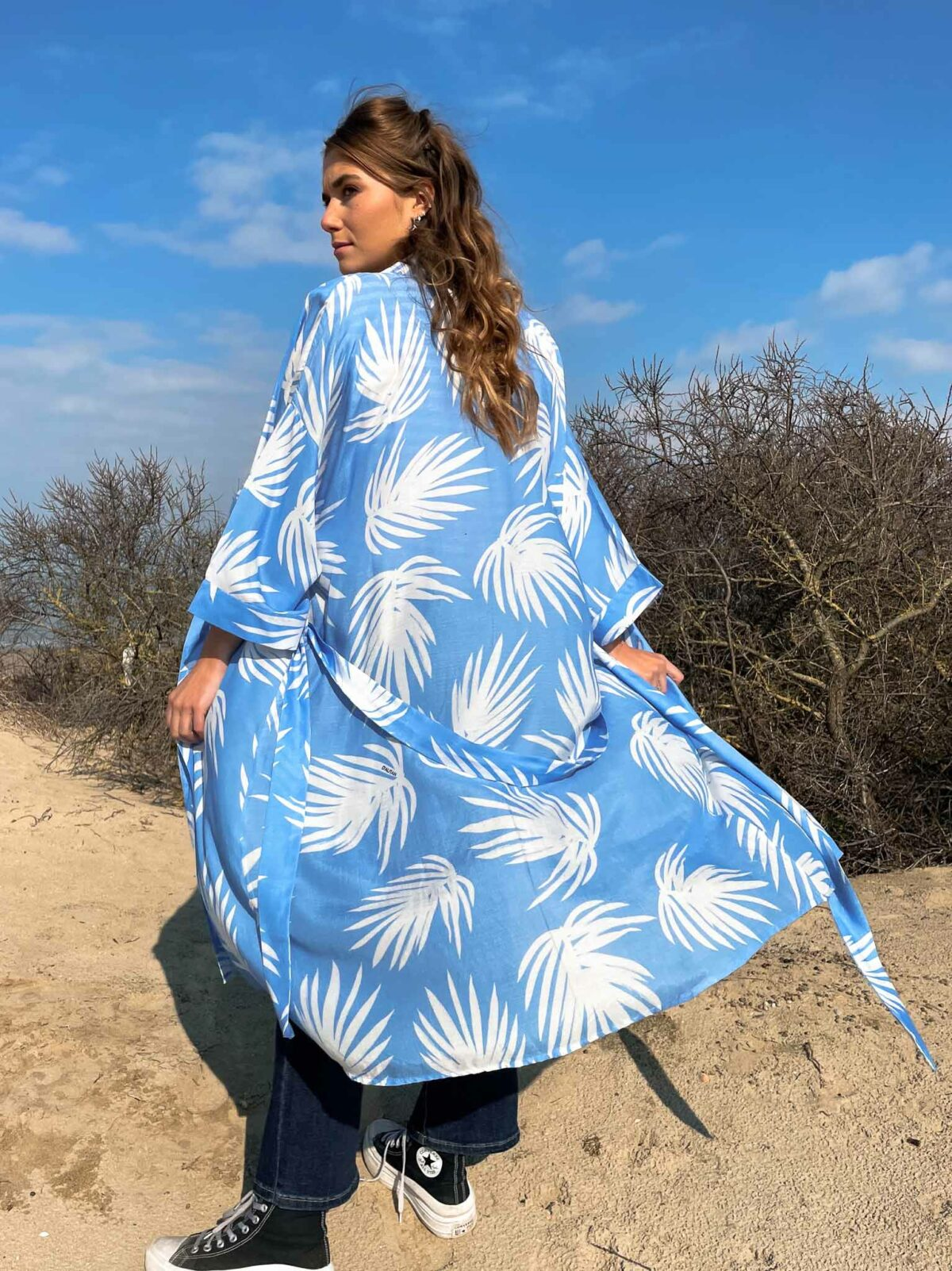 woman on the beach wearing a blue and white kimono