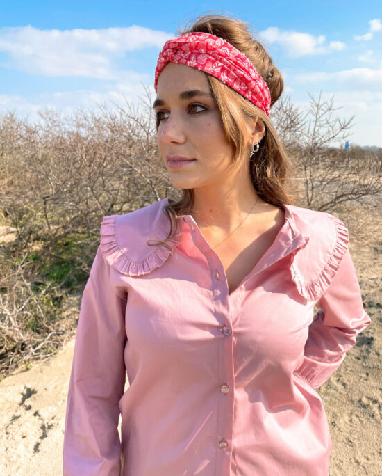 woman wearing a pink blouse and a pink hairband