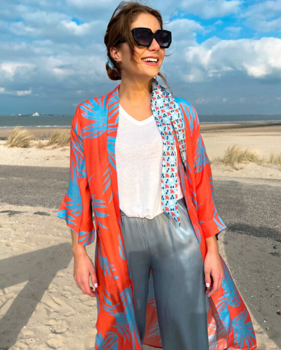 woman on the beach wearing an orange and blue kimono