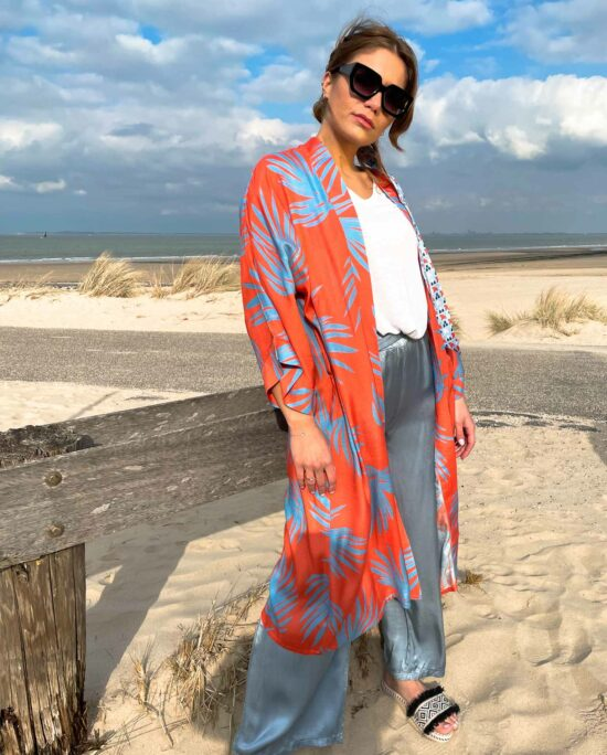 woman on the beach wearing an orange and blue kimono