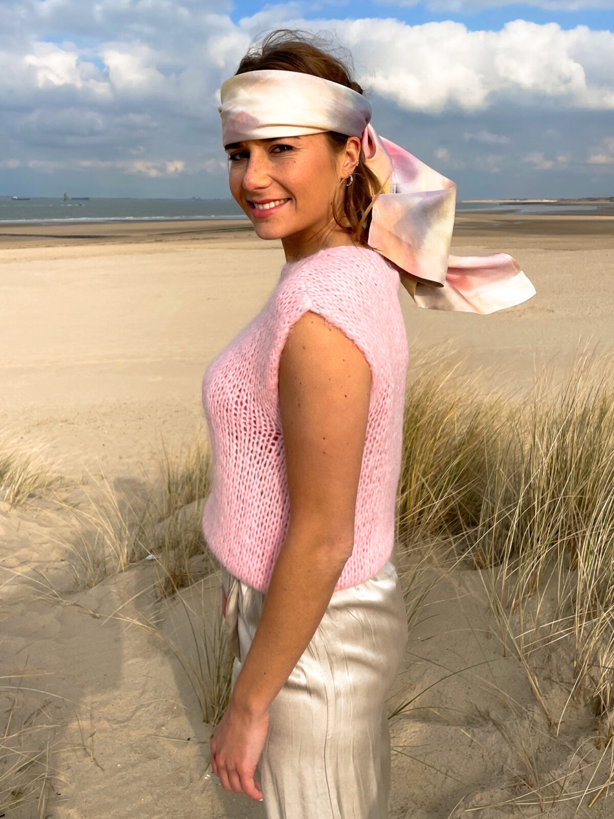 woman with a pink knitted top and a satin scarf on her head