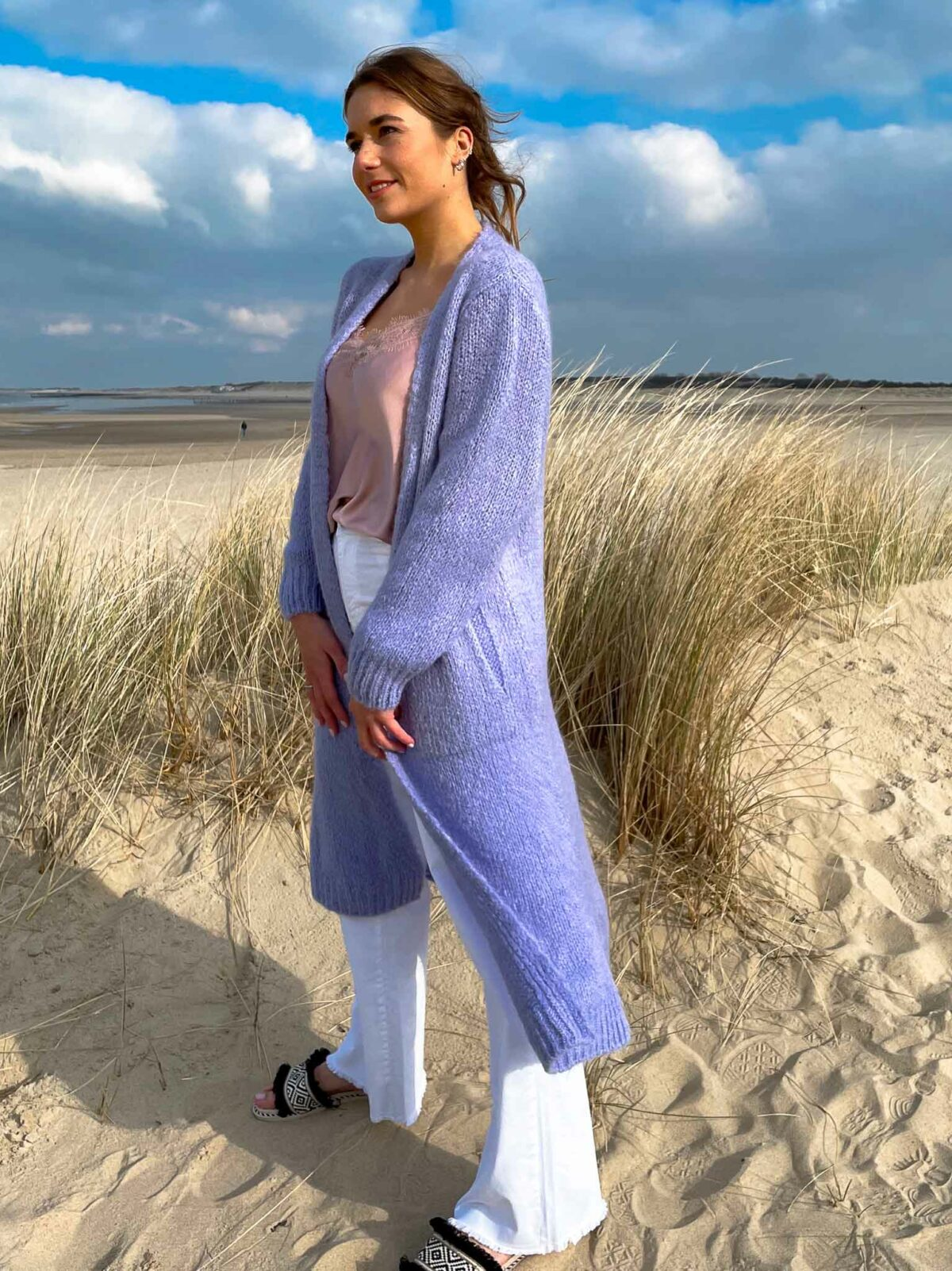 woman on the beach wearing a lilac long cardigan