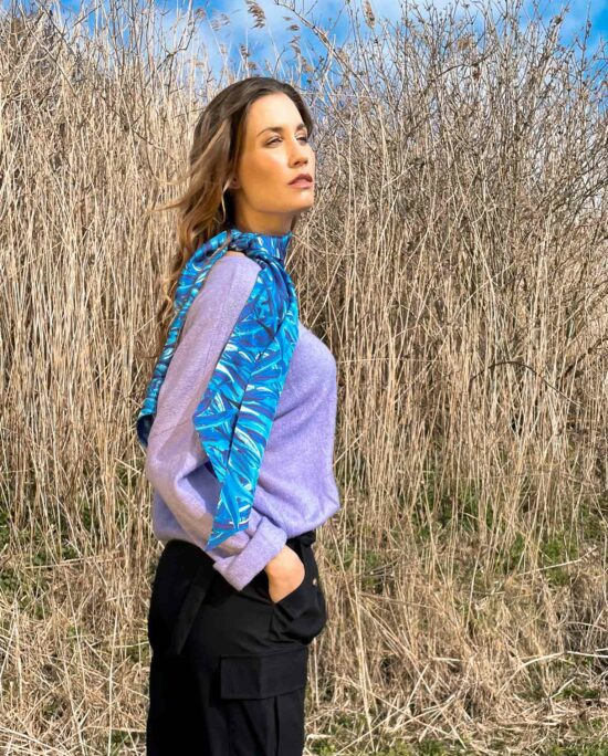 woman with a blue scarf and a lilac knitted sweater