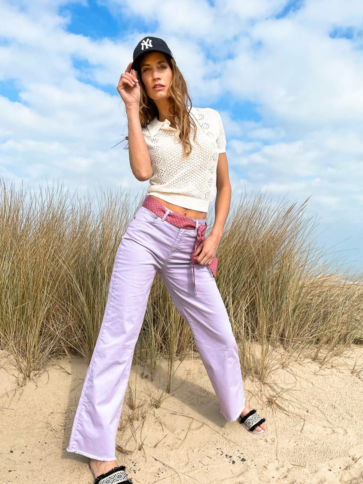 woman on the beach wearing lilac pants and a white polo