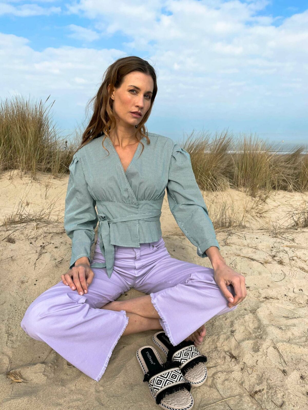 woman sitting down wearing a green top and lilac pants