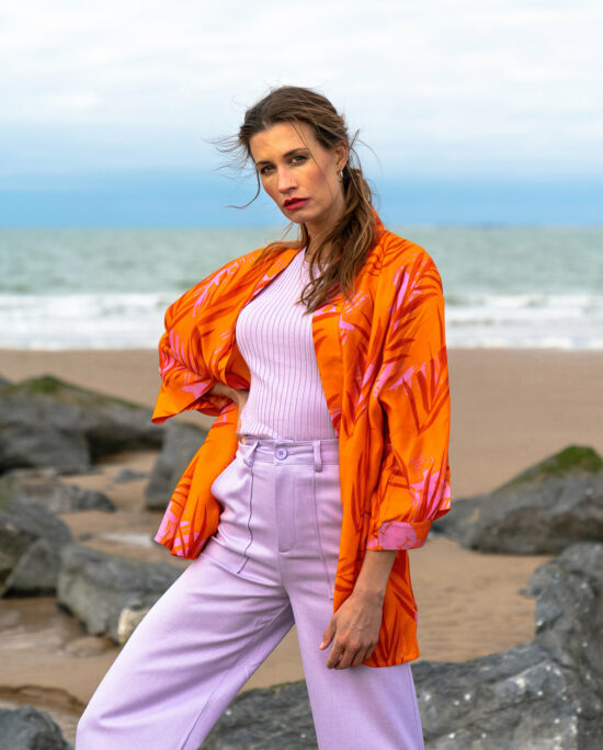 woman with a lilac top lilac pants and an orange kimono