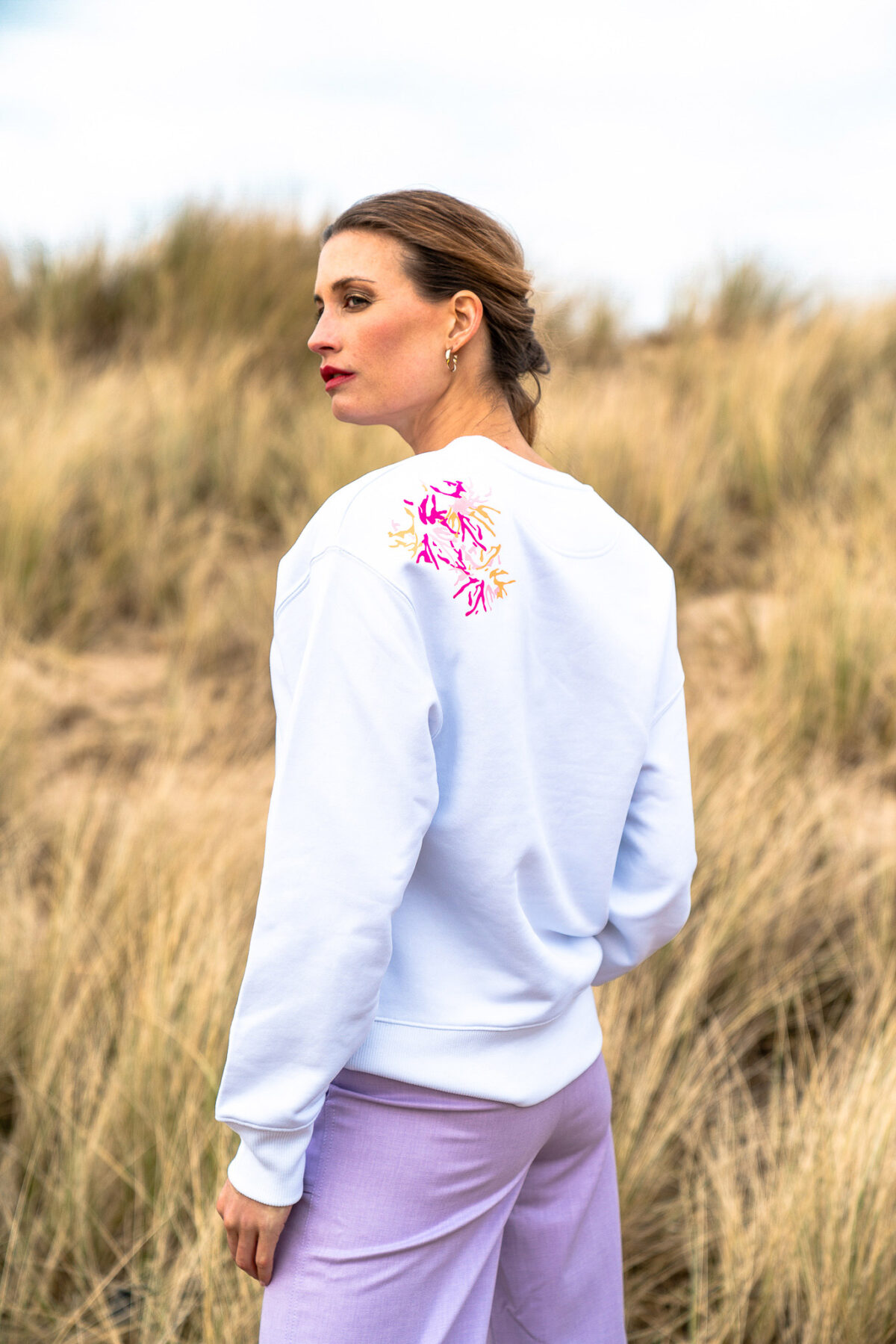 woman on the beach wearing a white sweater and lilac pants