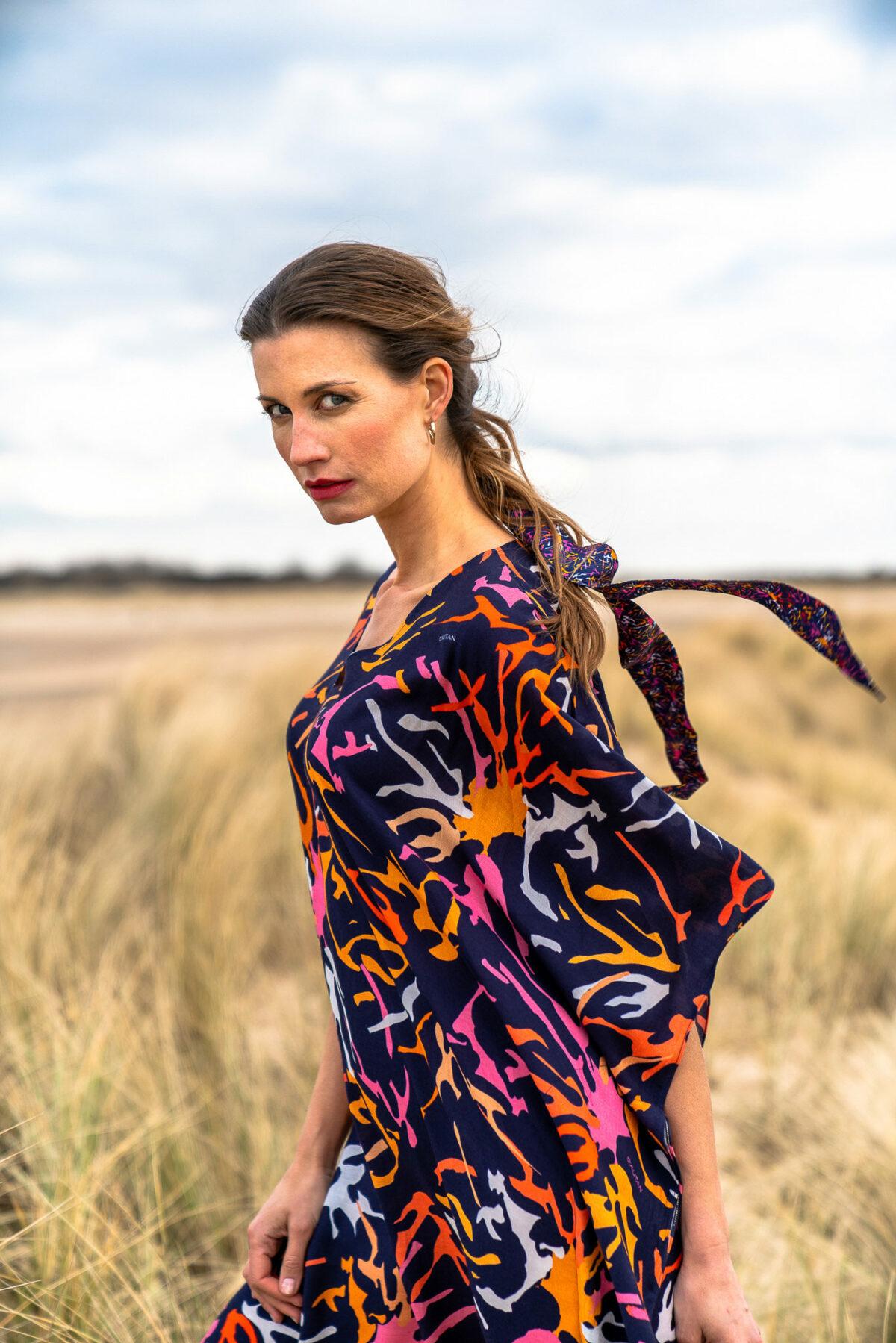 woman with a blue kaftan dress on the beach