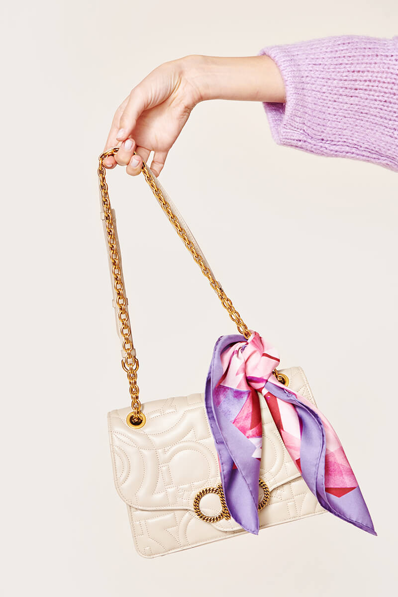 white purse with a pink and purple scarf