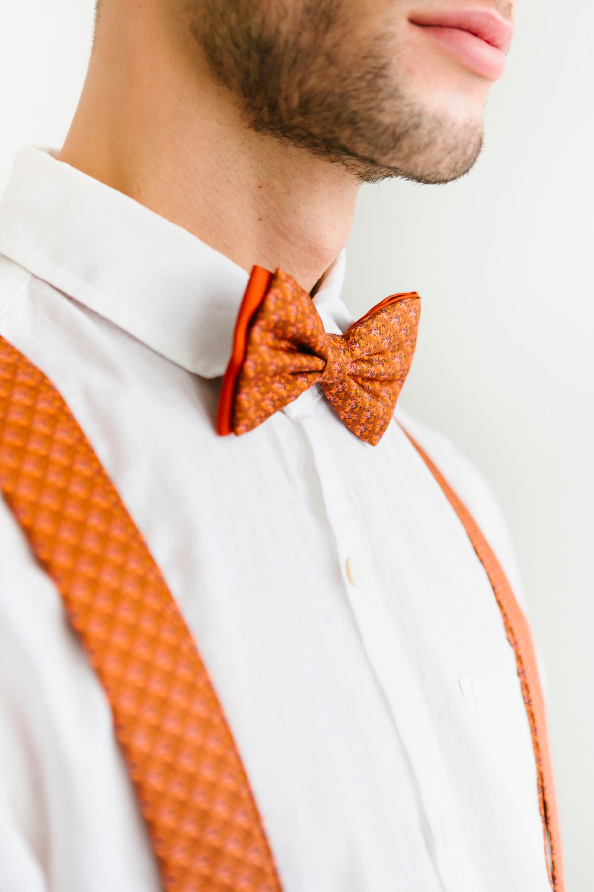 man with rusty orange bowtie and suspenders