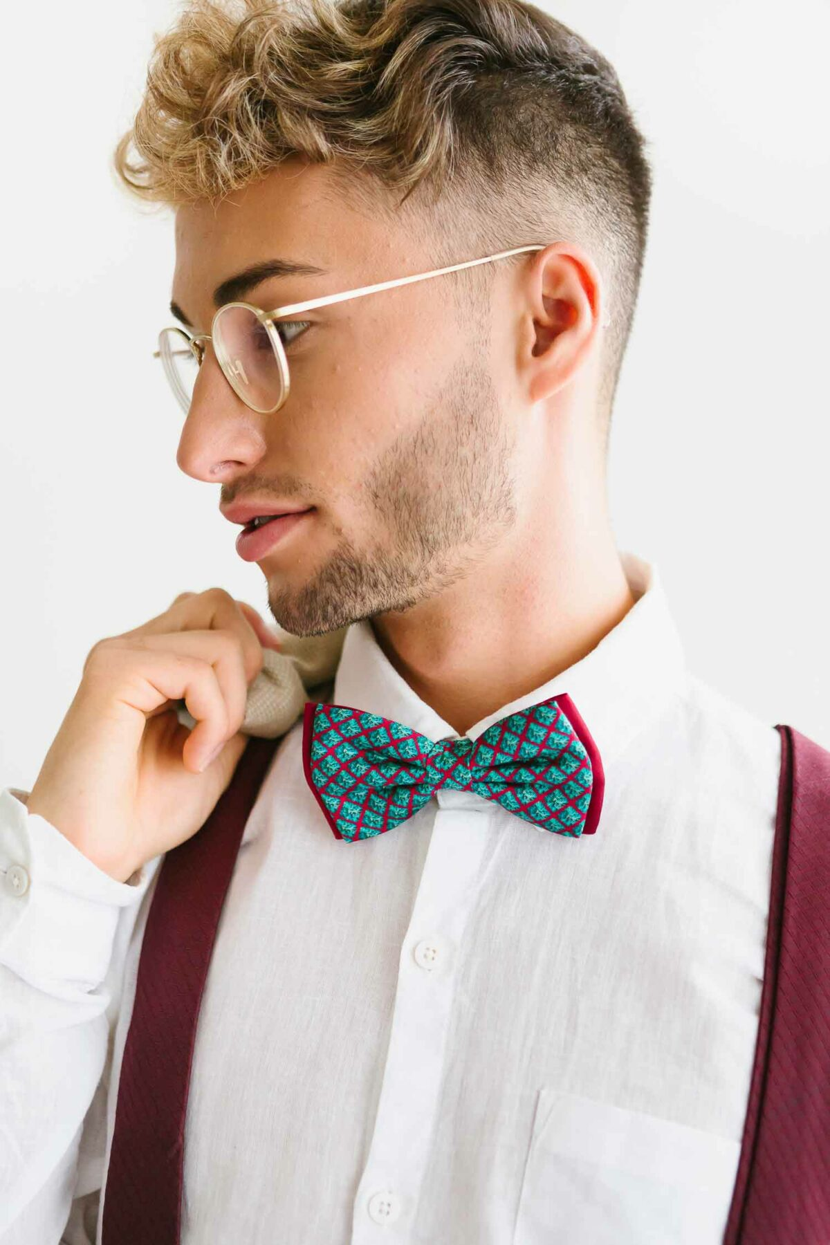 man with bordeaux red suspenders and a blue bowtie