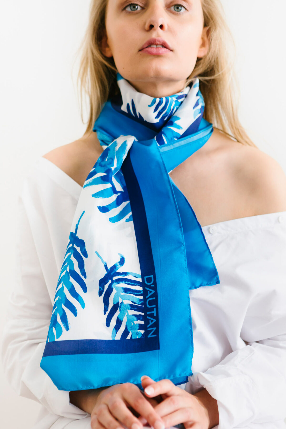 woman wearing a blue and white scarf on her neck