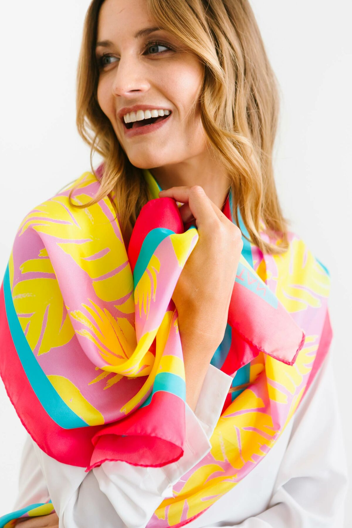 laughing woman wearing a colourful scarf