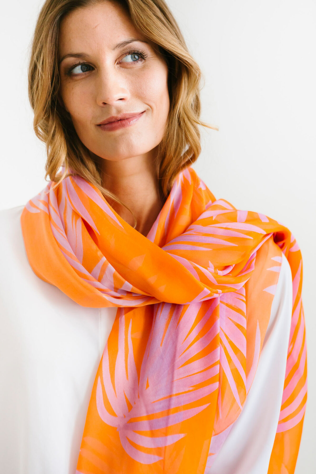 woman wearing an orange and pink scarf on her neck