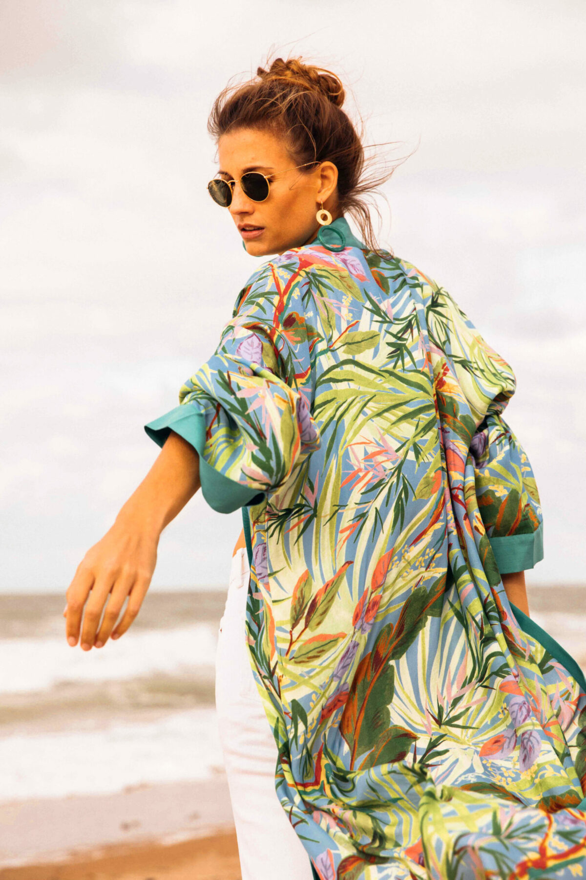 woman on the beach wearing a green white and orange kimono