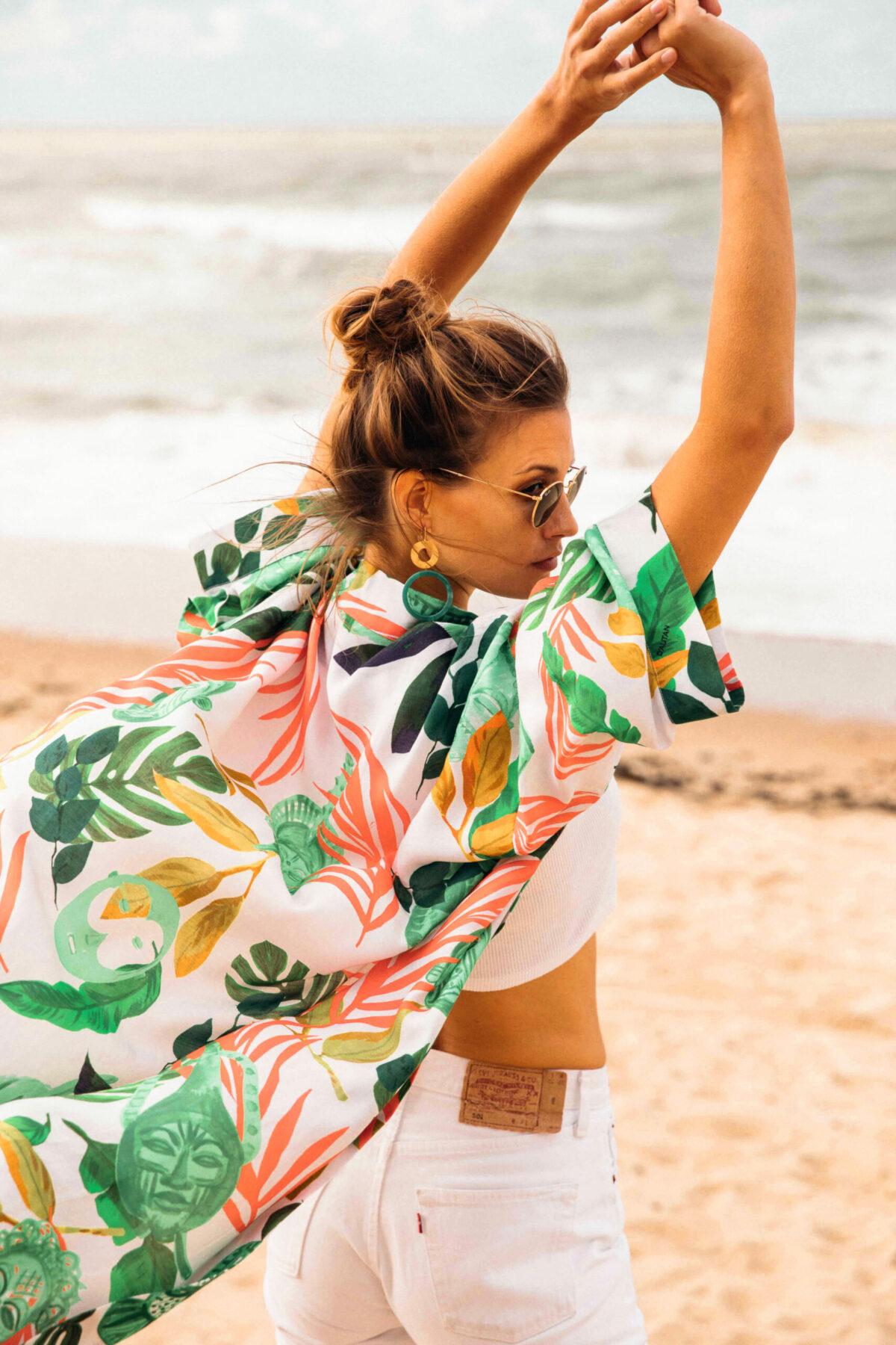 woman on the beach wearing a green white and orange kimono