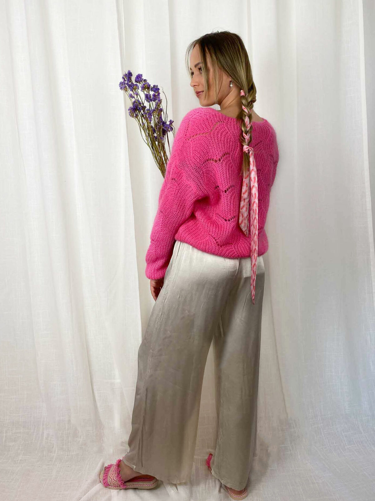 woman with a pink cardigan and champagne satin loose pants
