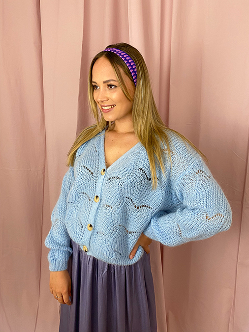 woman with a light blue knitted cardigan and a long blue skirt
