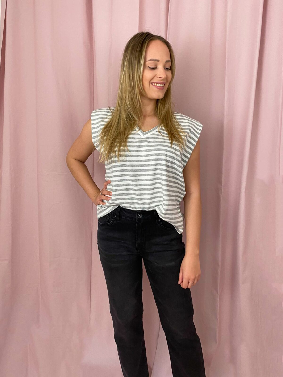 woman with striped top and black denim pants