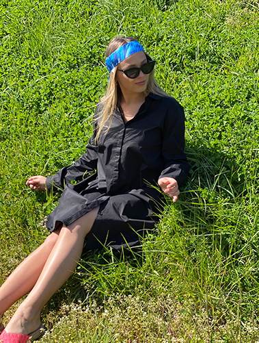 woman with a black dress and a blue ribbon in her hair in a grass field
