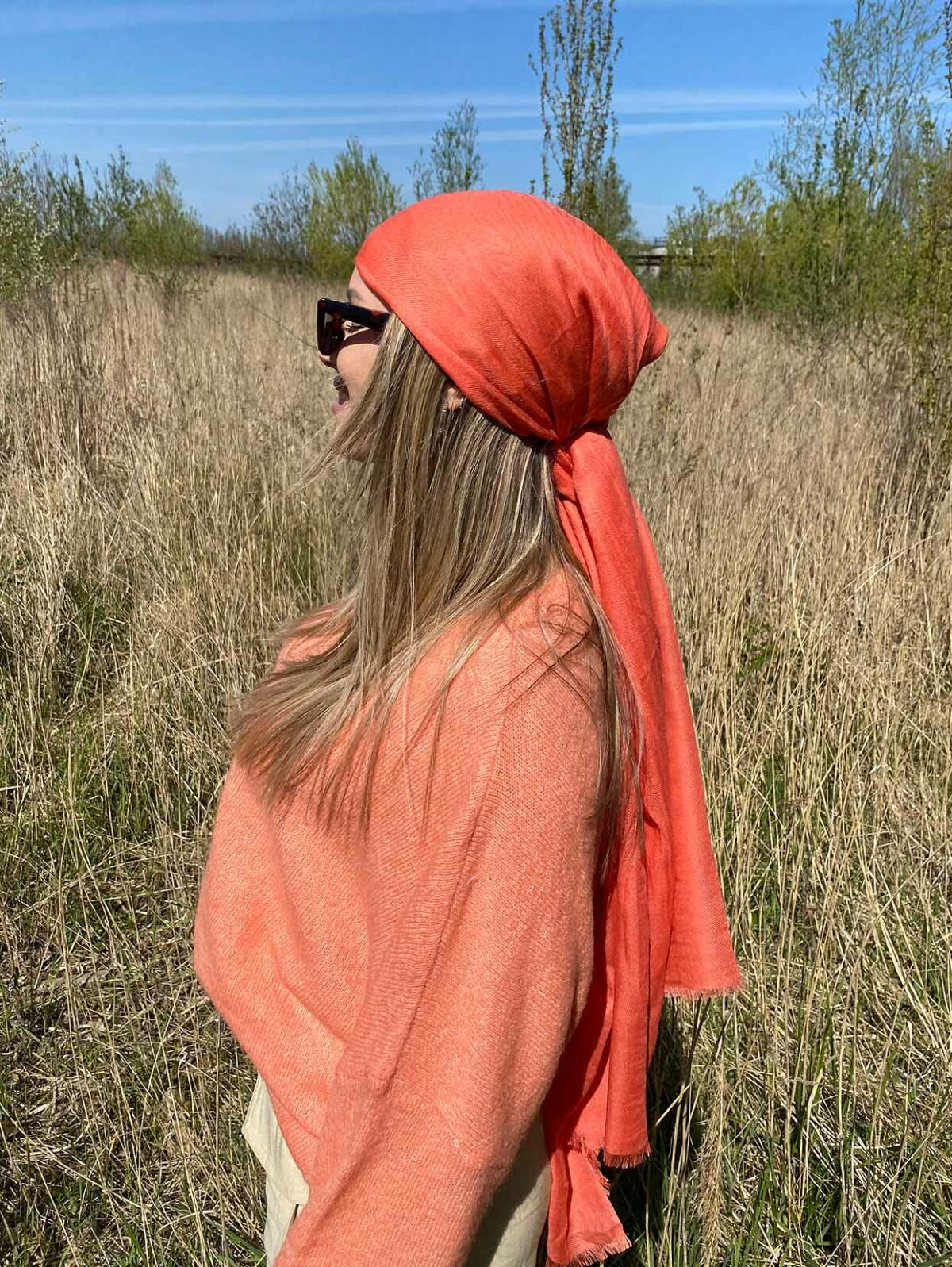 woman with a mandarin knitted sweater and a orange scarf on her head