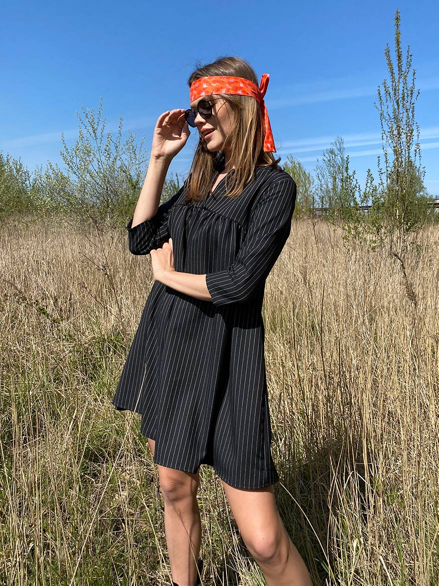 woman with a black dress and an orange hair ribbon