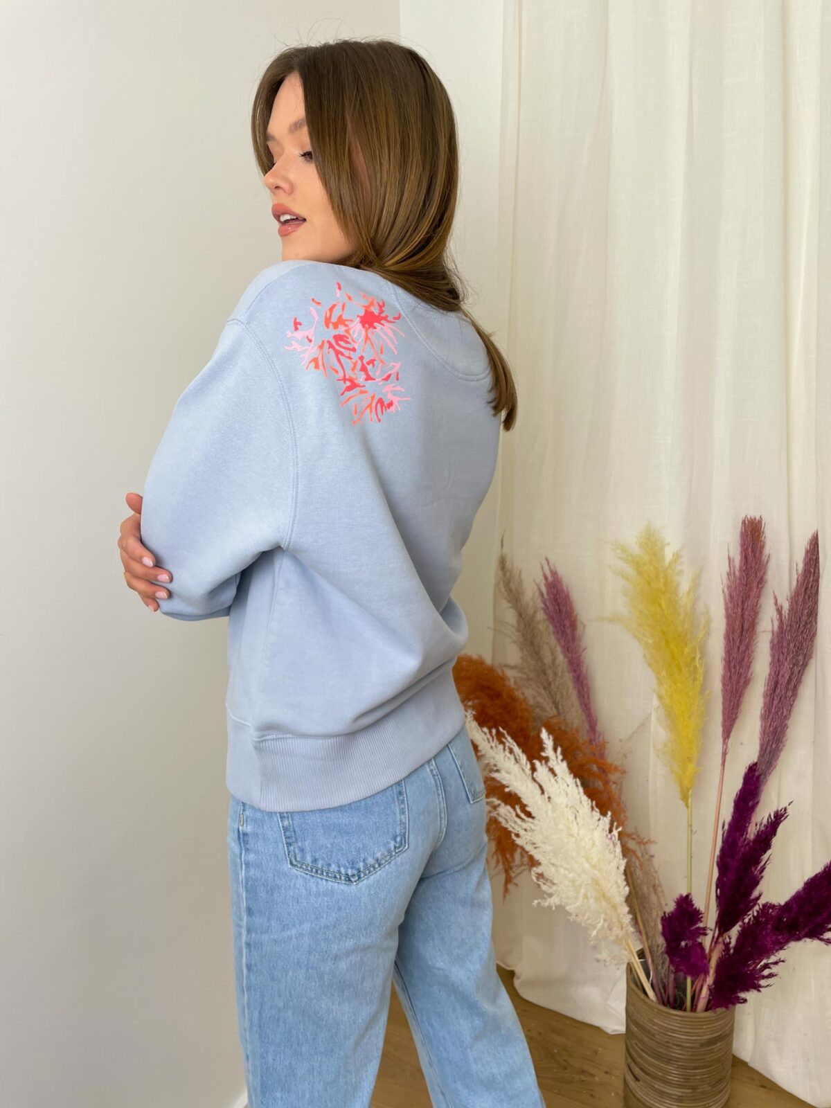 woman with a light blue sweater and denim pants