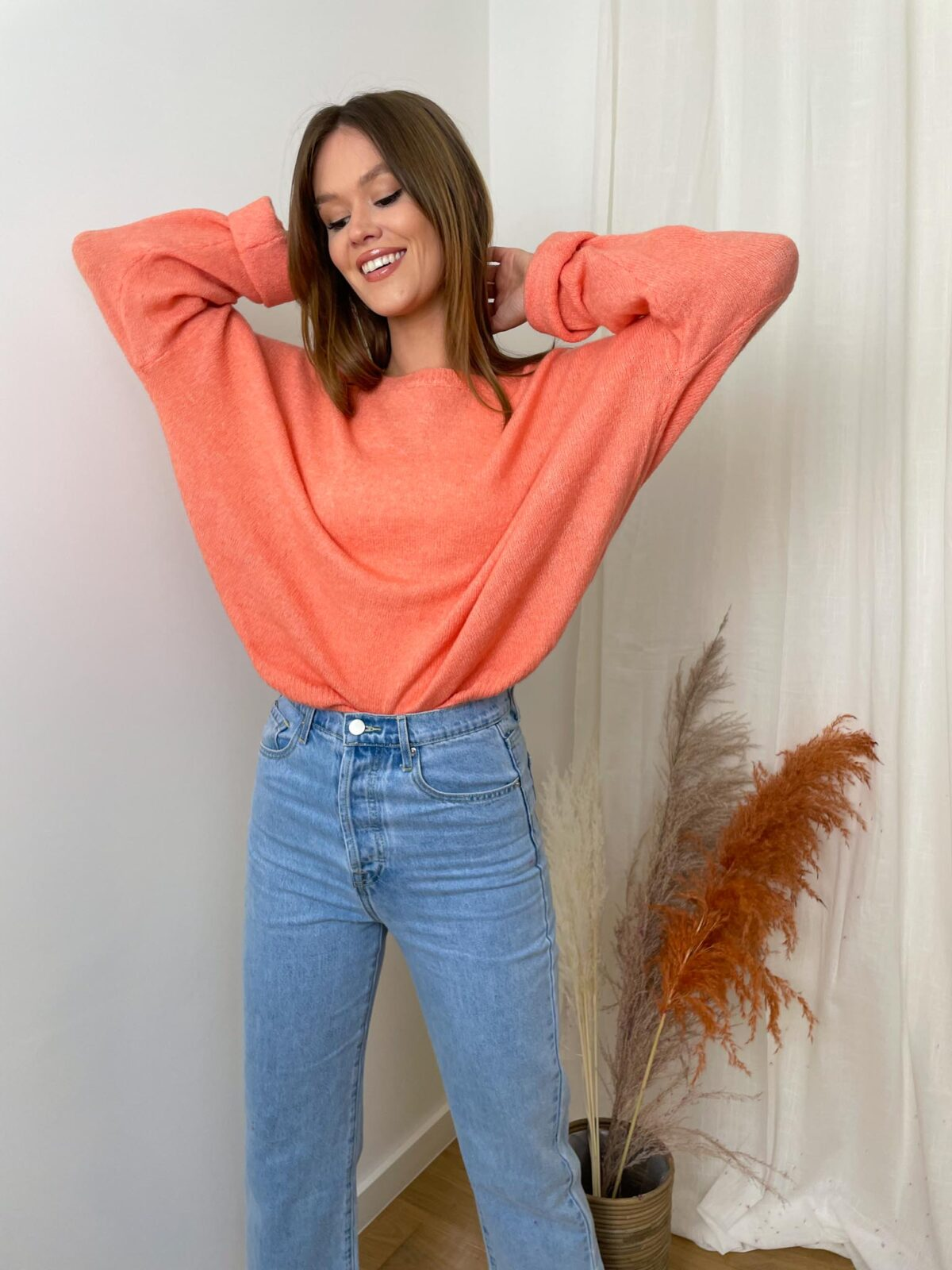 woman with an orange knitted sweater and denim pants