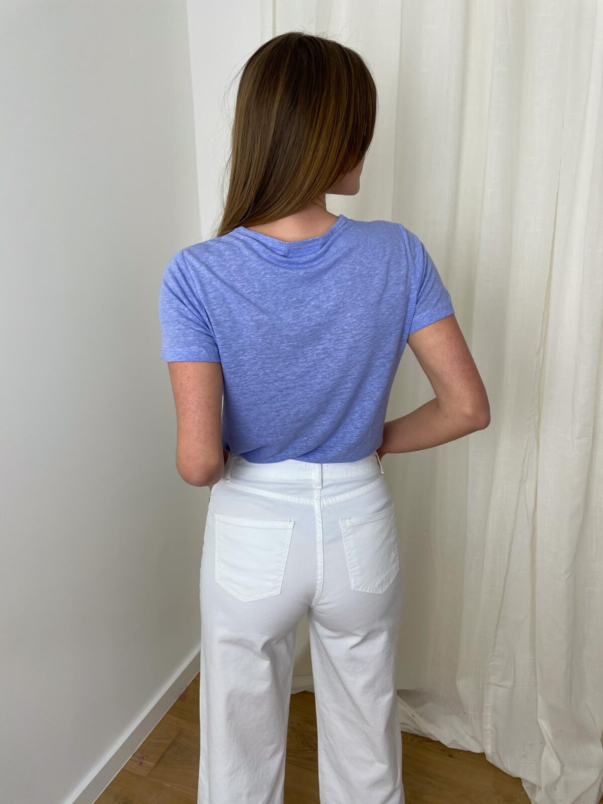 woman with a purple tshirt and white denim pants