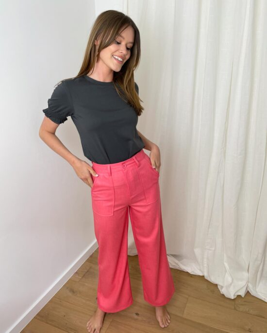 woman with a grey tshirt and coral pants