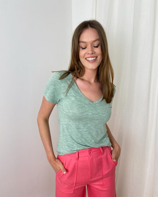 woman with a green tshirt and coral pants