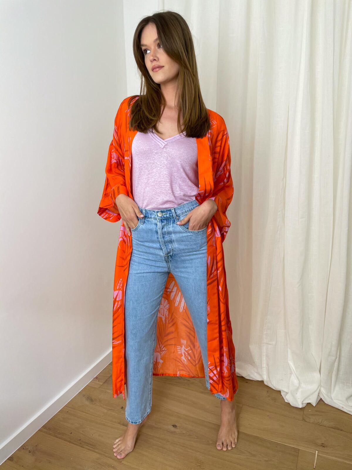 woman with an orange kimono and denim pants
