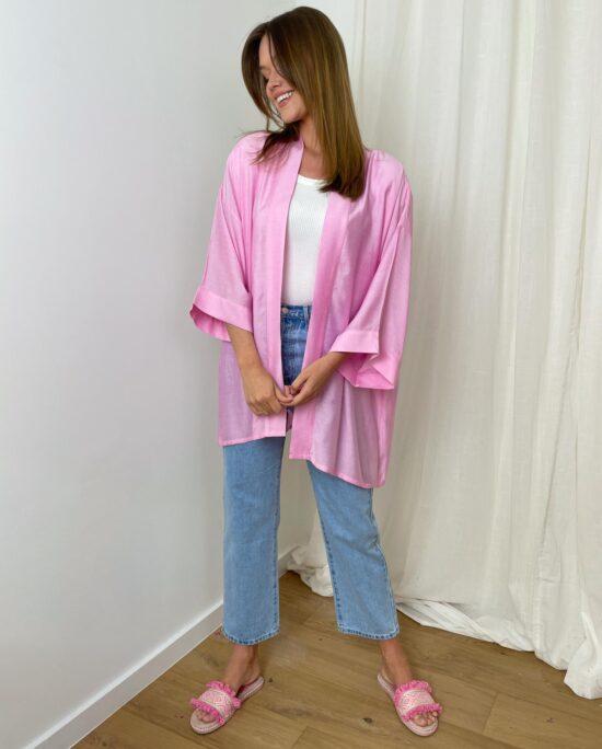 woman with a pink kimono and denim pants