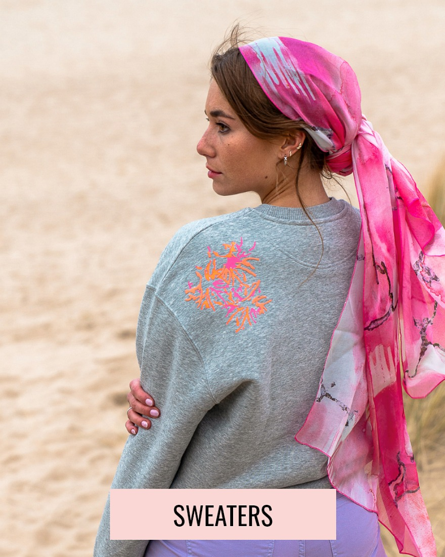 woman on the beach with a grey sweater and a pink scarf on her head
