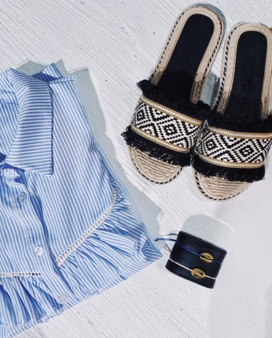 flatlay of black sandals and a blue blouse