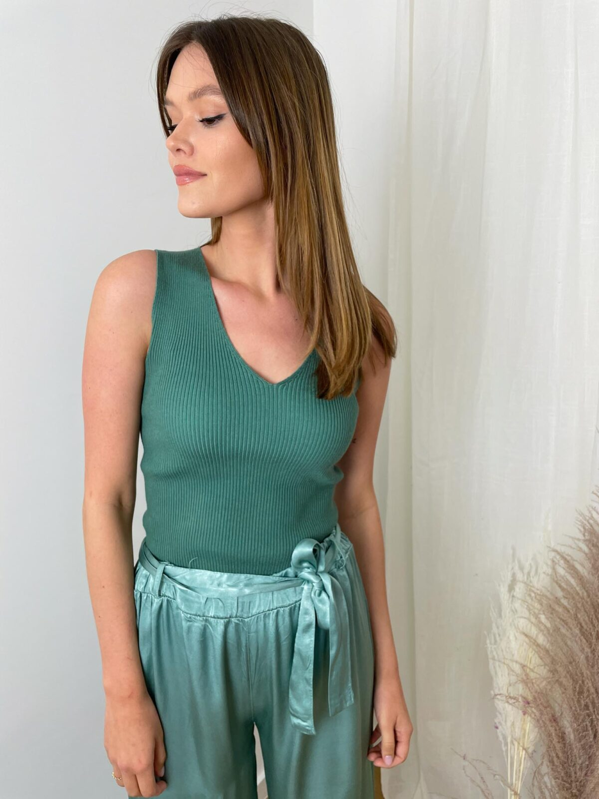 woman with a green top and green satin pants