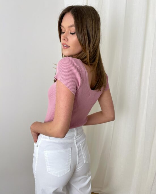 woman with white pants and a pink top